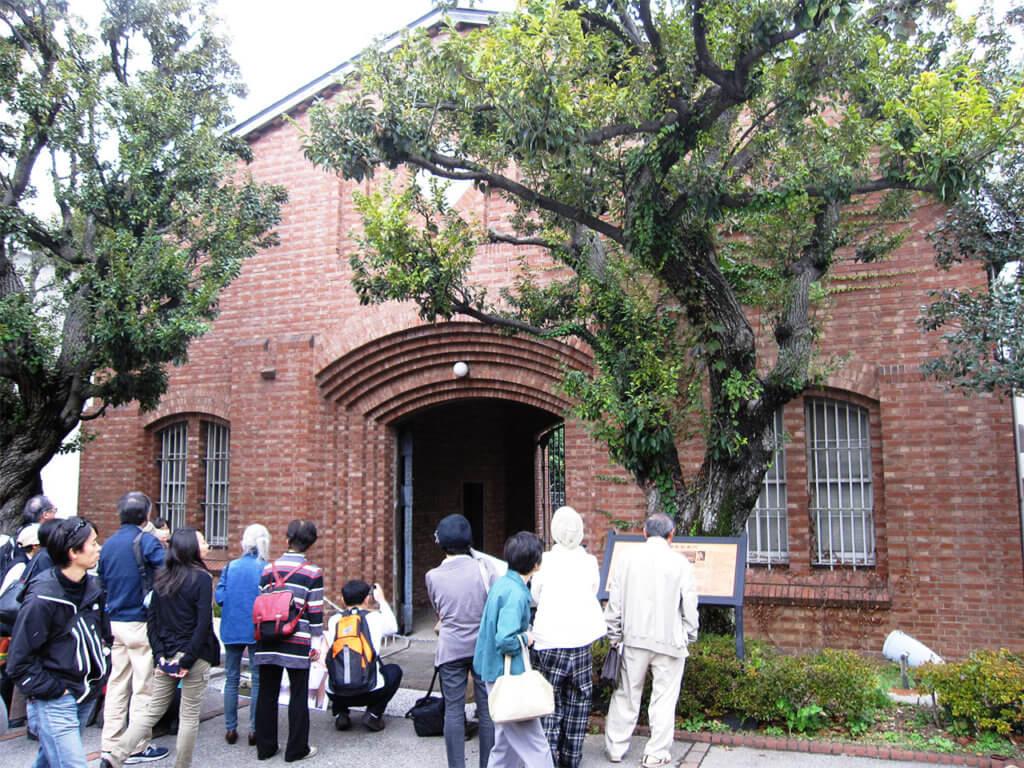 矯正研究所跡地に残る旧中野刑務所正門前で解説プレートを読む見学者たちの写真