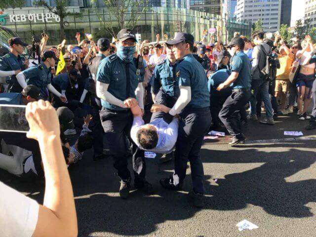 パレードの保守派を警察が排除している写真