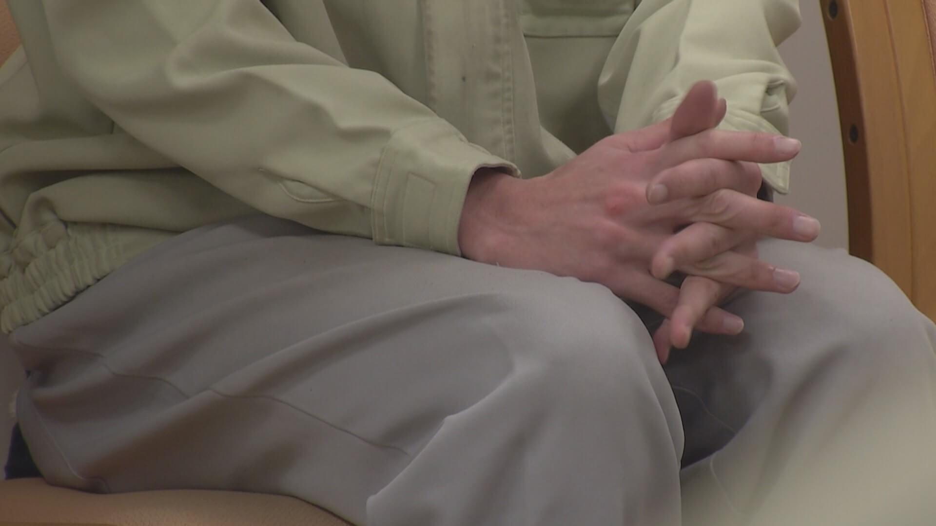 座っている服役者が指を組んでいる両手