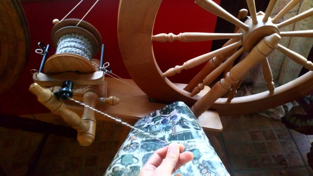 紡ぎ車で毛糸をひく